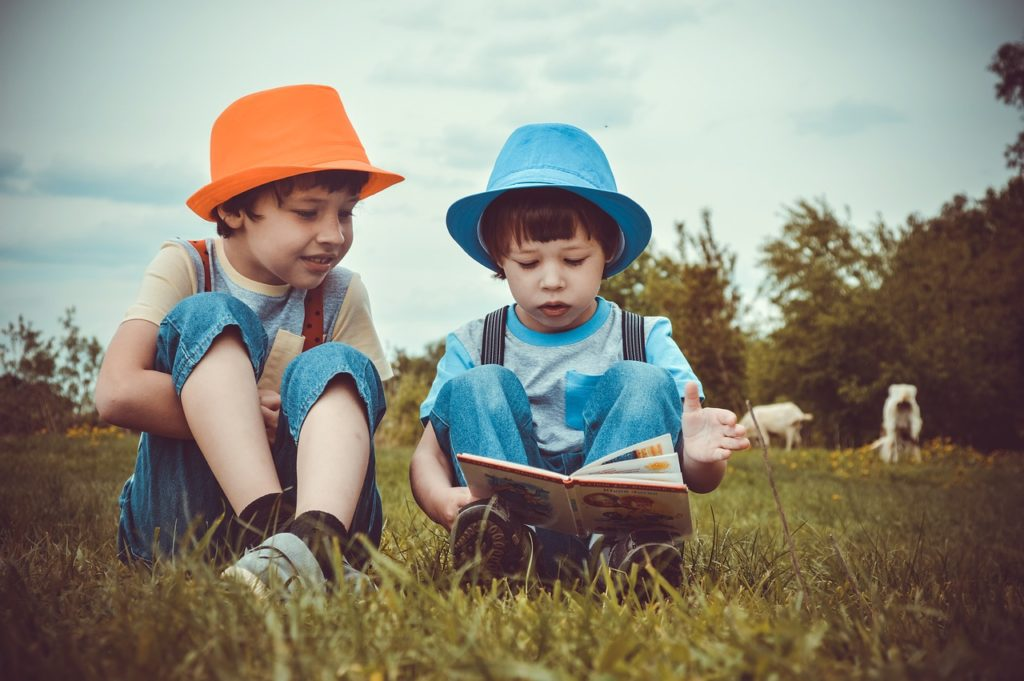 Two boys reading outdoors